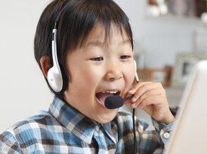 パソコンの前で笑う男の子